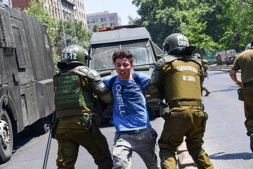 Policías someten a un manifestante en una protesta en Santiago