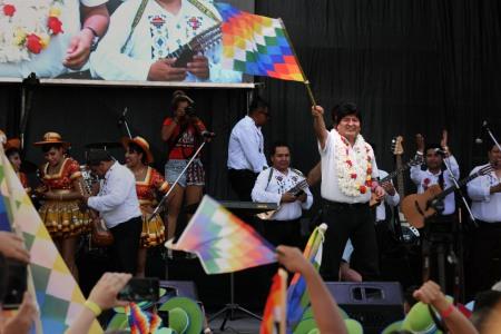 Evo Morales sube al escenario del club Deportivo Español flameando una Whipala. Ph Juan Ignacio Aréchaga